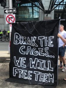 "Banner that says ""BREAK THE CAGES... WE WILL FREE THEM ALL"""